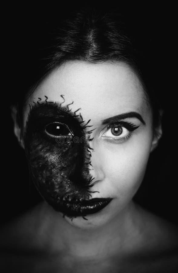 Retrato assustador do close-up de uma mulher com uma marca maldita em sua cara no fundo escuro imagem de stock royalty free