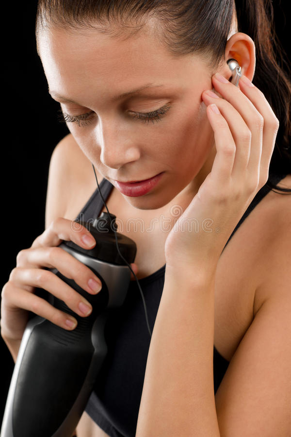 Retrato ativo da mulher com auscultadores da garrafa de água imagens de stock