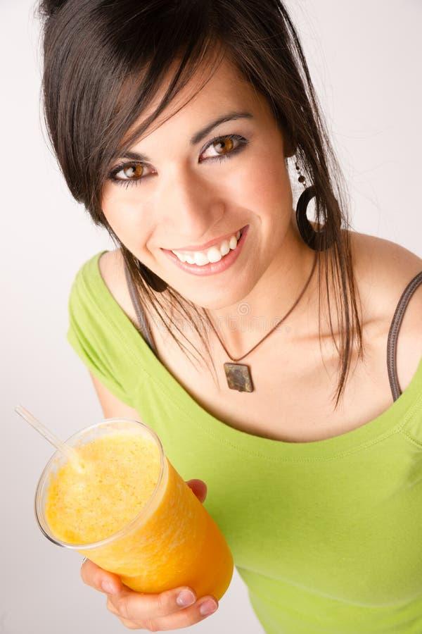 Retrato atrativo do íntimo da mulher que bebe o batido de fruta alaranjado imagem de stock royalty free