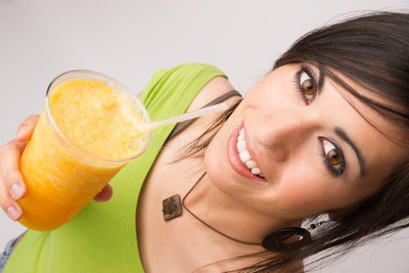 Retrato atrativo do íntimo da mulher que bebe o fruto alaranjado Smoothi foto de stock