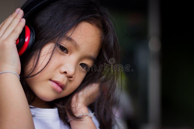 Retrato, auriculares que llevan de la muchacha, feliz, escuchando la música imagenes de archivo