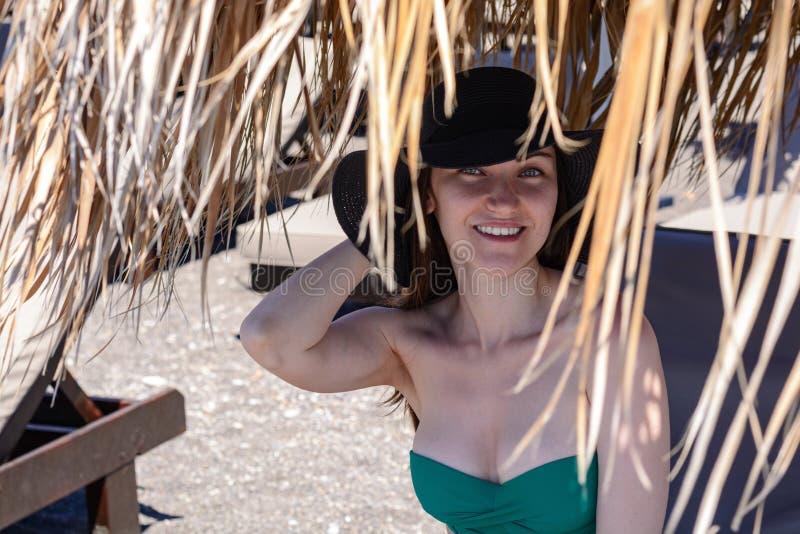 Retrato auténtico de una mujer joven a través de un paraguas de la paja del sol, sonrisa linda el vacaciones fotos de archivo