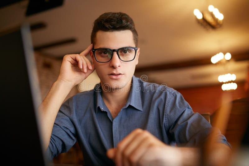 Retrato autêntico do homem de negócios seguro novo que olha a câmera com o portátil no escritório Homem do moderno nos vidros e fotografia de stock