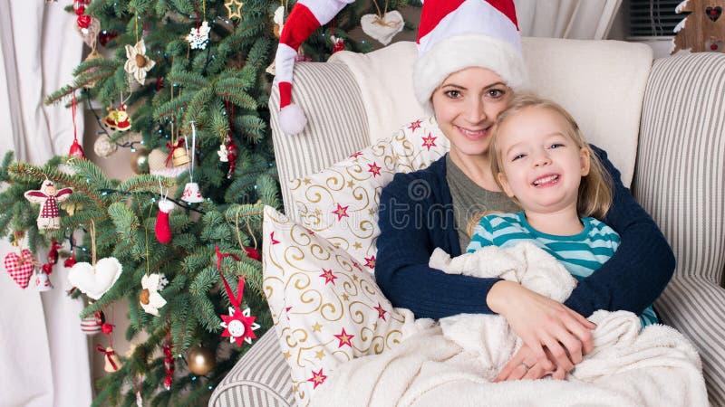 Retrato autêntico do Natal da família na frente da árvore do xmas Mãe e filha de sorriso no Natal imagens de stock royalty free