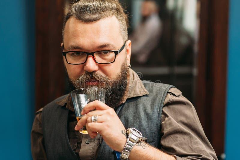 Retrato bebendo do uísque do homem farpado fotografia de stock royalty free