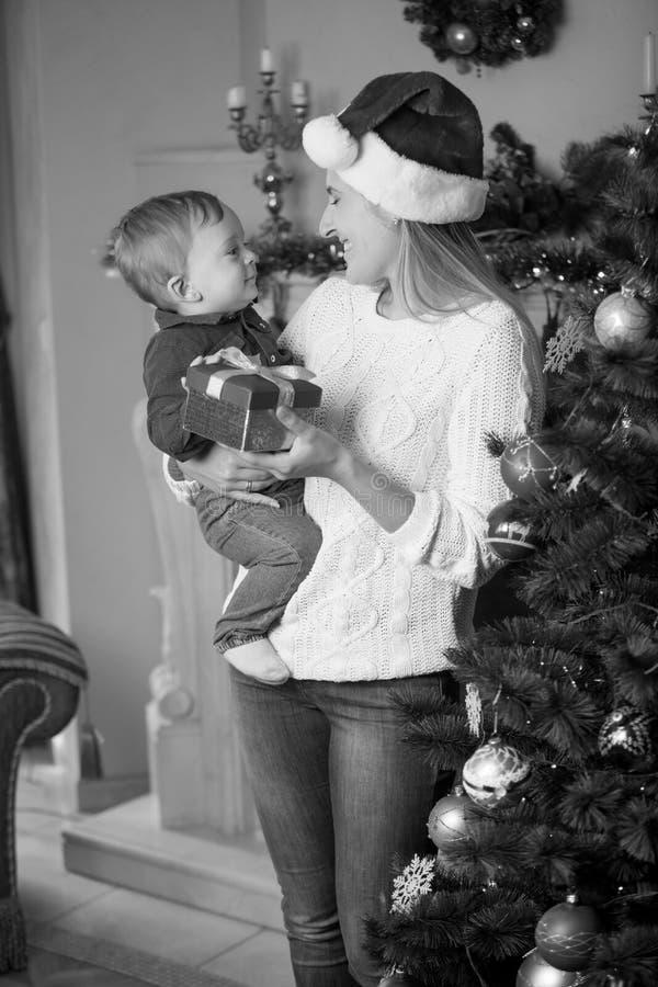 Retrato blanco y negro de la madre joven feliz en el sombrero de Papá Noel y imagen de archivo libre de regalías