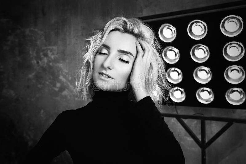 Retrato blanco y negro de la muchacha rizada atractiva hermosa elegante joven en suéter negro en la etapa imagenes de archivo