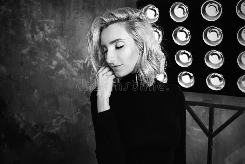 Retrato blanco y negro de la muchacha rizada atractiva hermosa elegante joven en suéter negro en la etapa fotografía de archivo libre de regalías