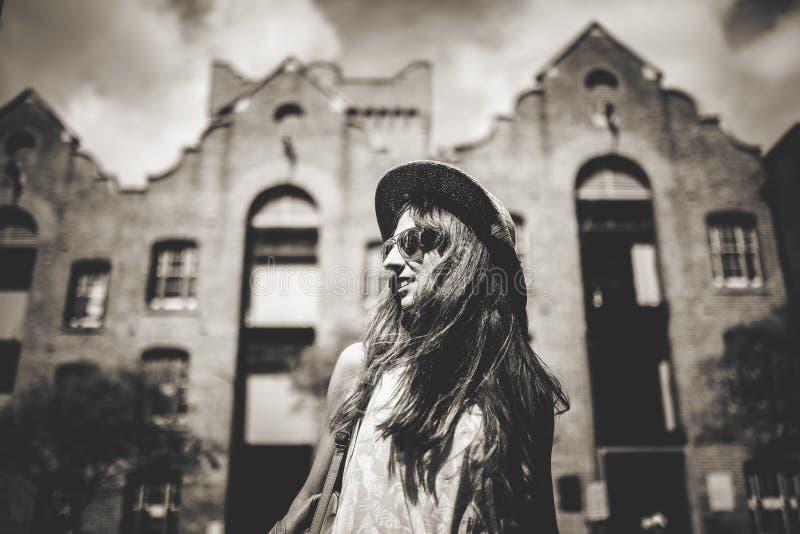 Retrato blanco y negro de la muchacha sonriente linda en gafas de sol con los edificios de la ciudad en el fondo fotos de archivo