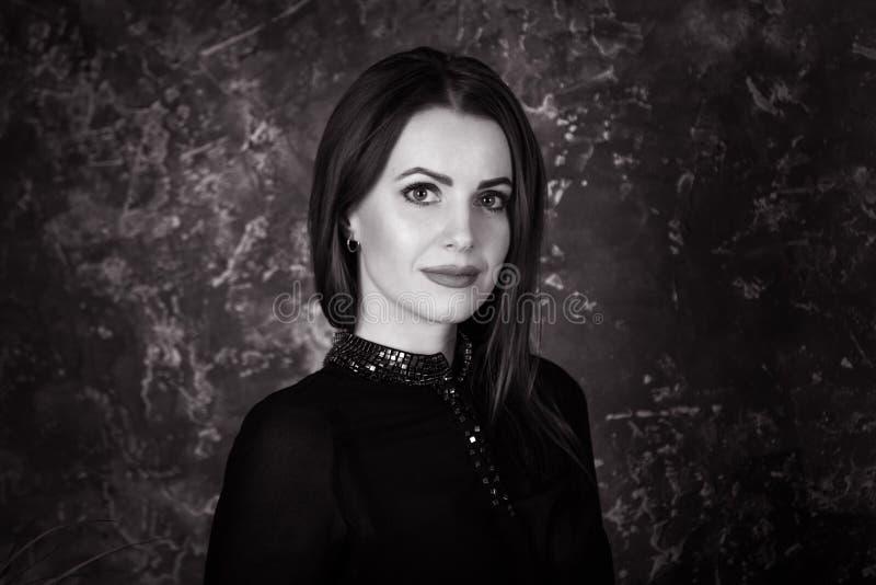 Retrato blanco y negro de la mujer morena joven hermosa que se sienta en dormitorio foto de archivo