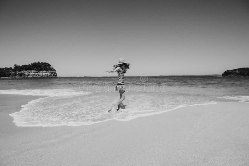 Retrato blanco y negro de la mujer que goza y que baila en la playa imagenes de archivo