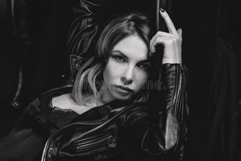 Retrato blanco y negro de la mujer rubia atractiva en el vestido de seda y la chaqueta negra imagen de archivo