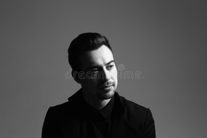 Retrato blanco y negro de un hombre hermoso joven serio en un traje, iluminación dramática imágenes de archivo libres de regalías