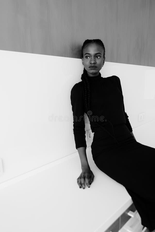 Retrato blanco y negro de una mujer americana africana o negra seria que se coloca sobre fondo gris y que mira lejos imágenes de archivo libres de regalías