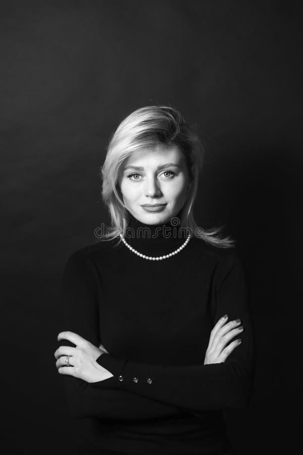 Retrato blanco y negro de una mujer de negocios joven, brazos del estudio doblados fotografía de archivo