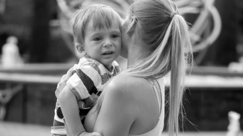 Retrato blanco y negro del griterío 3 años del niño pequeño que abraza a su madre en parque fotografía de archivo