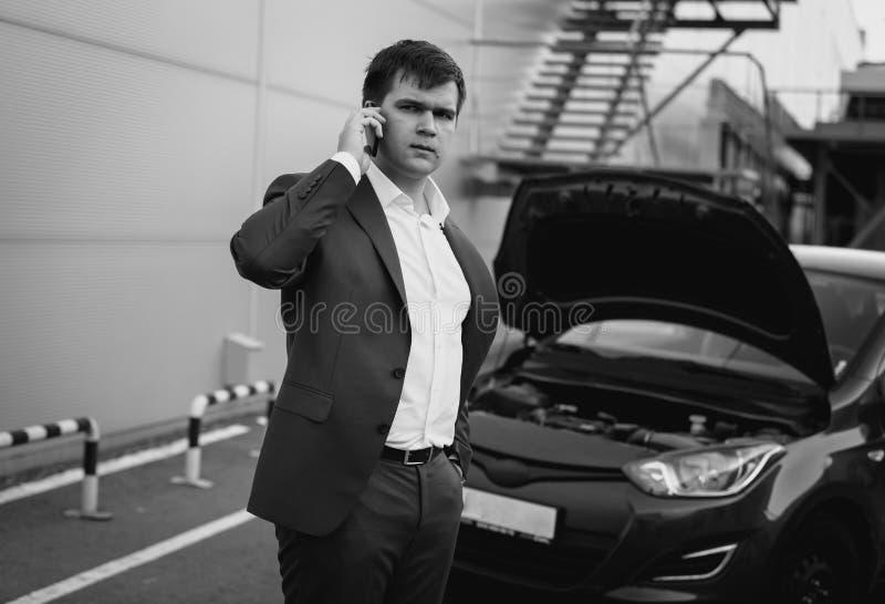 Retrato blanco y negro del hombre que llama por el teléfono al servicio del coche fotos de archivo libres de regalías