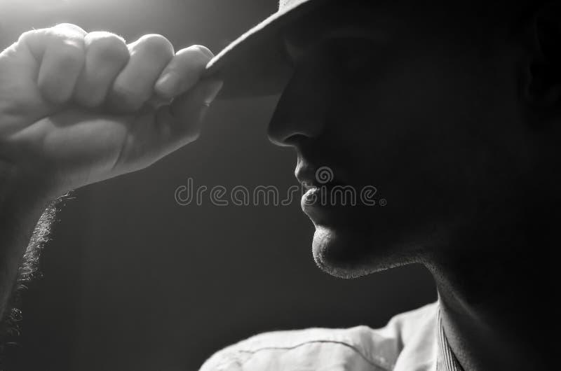 Retrato blanco y negro del perfil de un hombre atractivo fuerte en un sombrero imágenes de archivo libres de regalías
