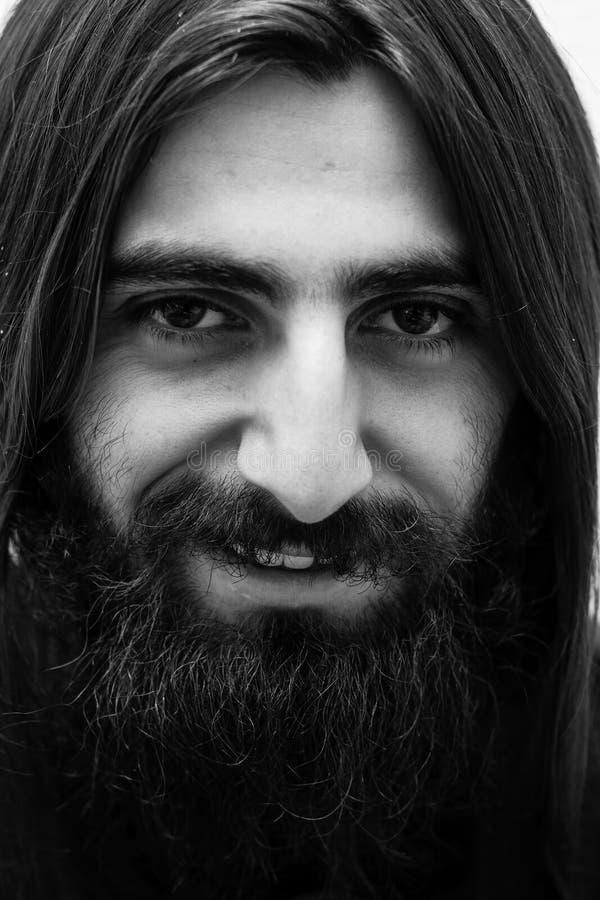 Retrato blanco y negro del primer de un hombre barbudo con el pelo largo fotografía de archivo