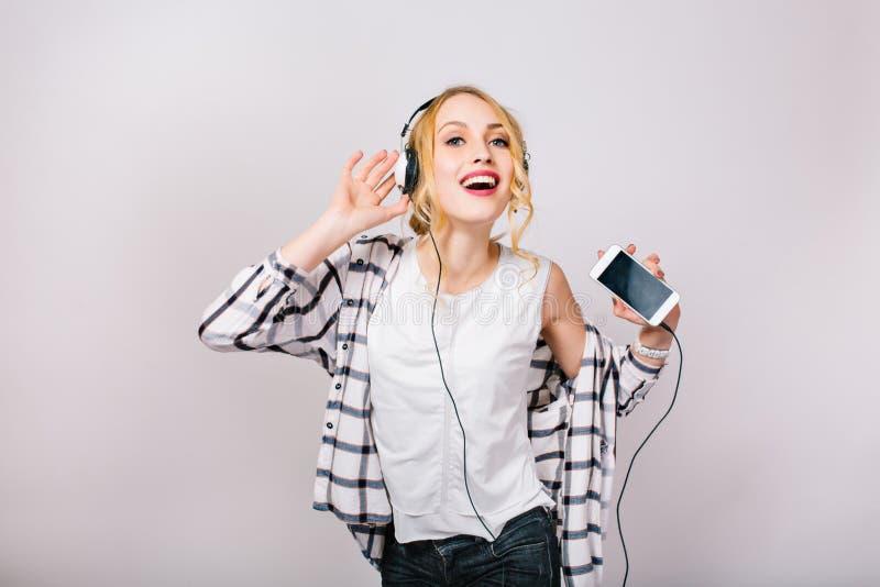 Retrato bonito agradável da mulher lindo deleitada com cabelo louro Dança feliz da menina da música contra o cinza isolado fotografia de stock royalty free