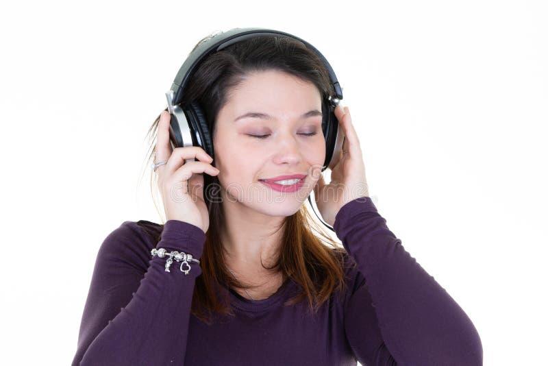 Retrato bonito da jovem mulher com os olhos fechados que levantam em fones de ouvido profissionais do DJ no fundo branco foto de stock