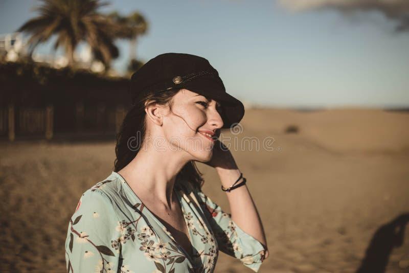 Retrato bonito da jovem mulher no deserto que toca em seu tampão preto fotos de stock royalty free