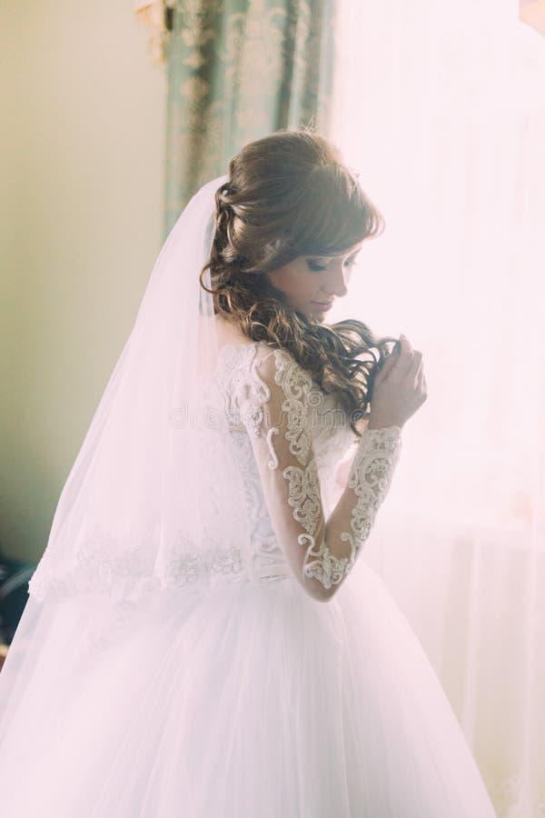 Retrato bonito da jovem mulher no vestido branco e do véu na manhã perto da janela Penteado encaracolado foto de stock