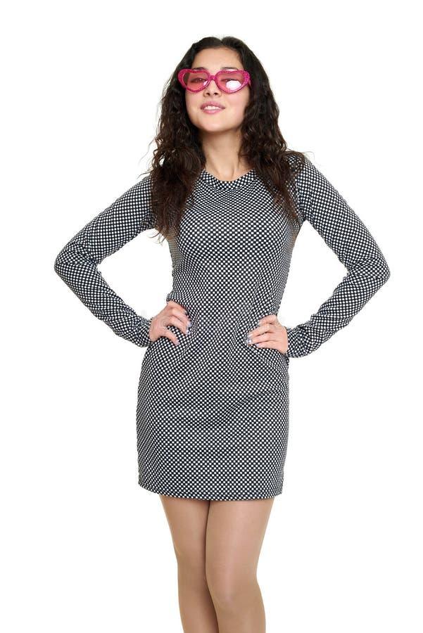 Retrato bonito da jovem mulher no vestido quadriculado preto e branco, óculos de sol cor-de-rosa na forma do coração, cabelo enca fotografia de stock royalty free