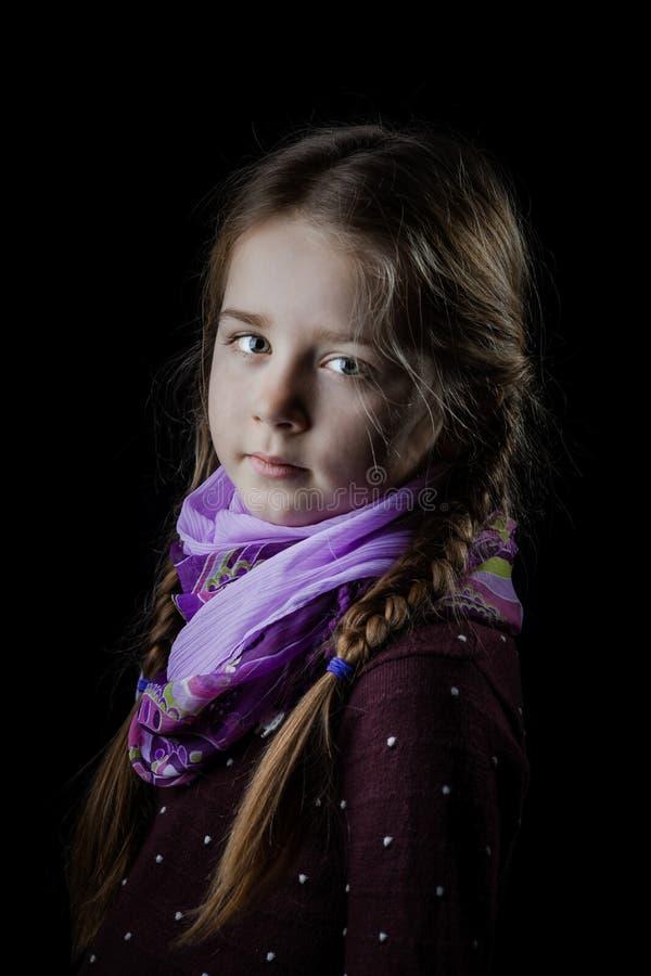 Retrato bonito da menina no fundo preto, seriamente criança imagem de stock