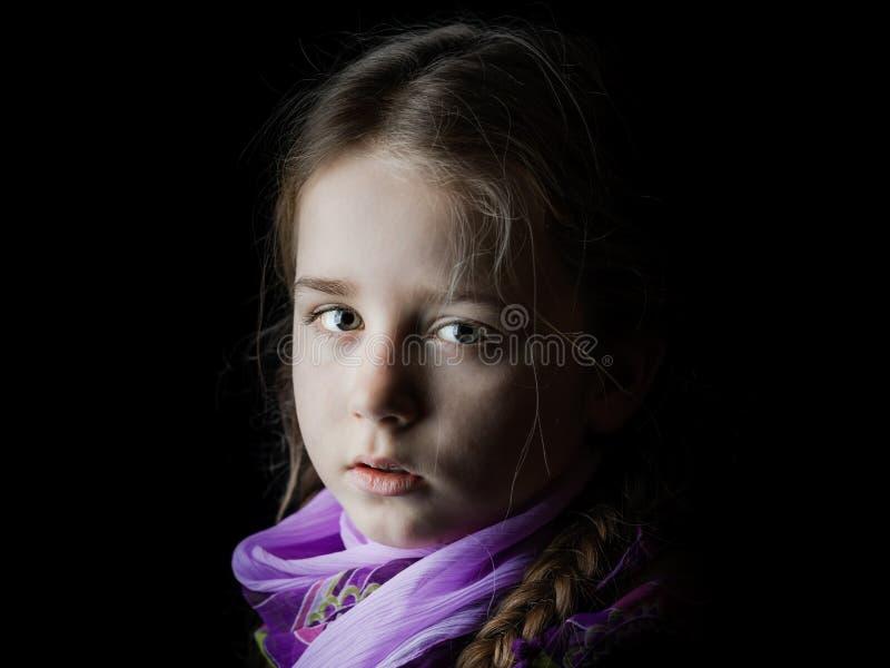 Retrato bonito da menina no fundo preto, seriamente criança imagem de stock royalty free