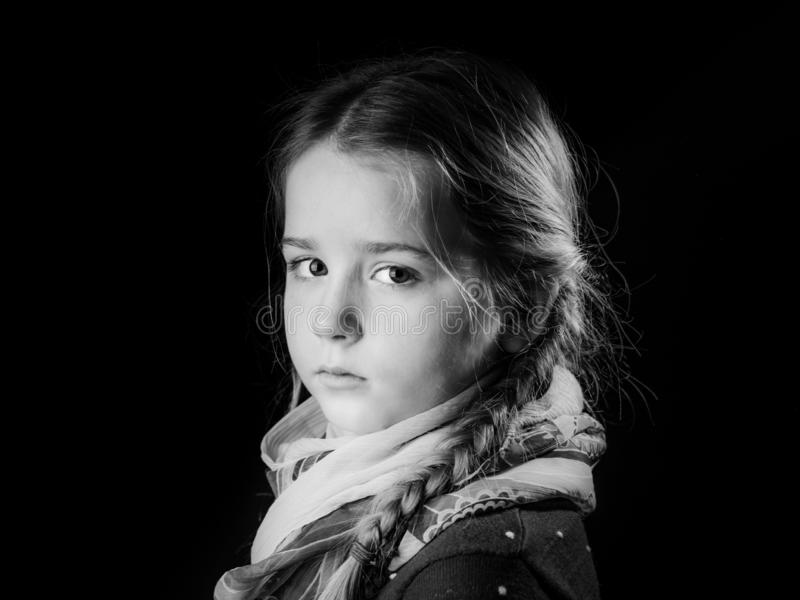 Retrato bonito da menina no fundo preto, seriamente criança foto de stock