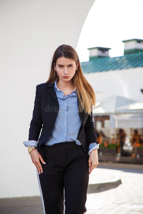 Retrato bonito da mulher com cabelo saudável longo Olhar do ` s das mulheres elegantes com revestimento preto e a blusa azul Form foto de stock