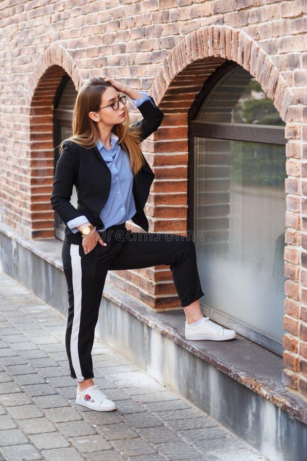 Retrato bonito da mulher com cabelo saudável longo Olhar do ` s das mulheres elegantes com revestimento preto e a blusa azul Form imagens de stock
