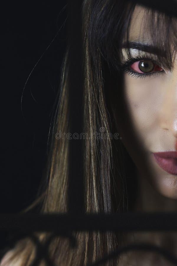 Retrato bonito da mulher do vampiro no preto foto de stock royalty free