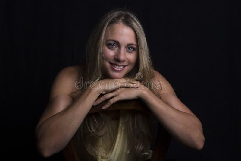 Retrato bonito da mulher na luminosidade reduzida com uma parte superior alaranjada foto de stock royalty free