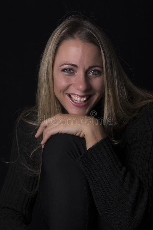 Retrato bonito da mulher na luminosidade reduzida que senta-se no sofá de couro marrom imagem de stock