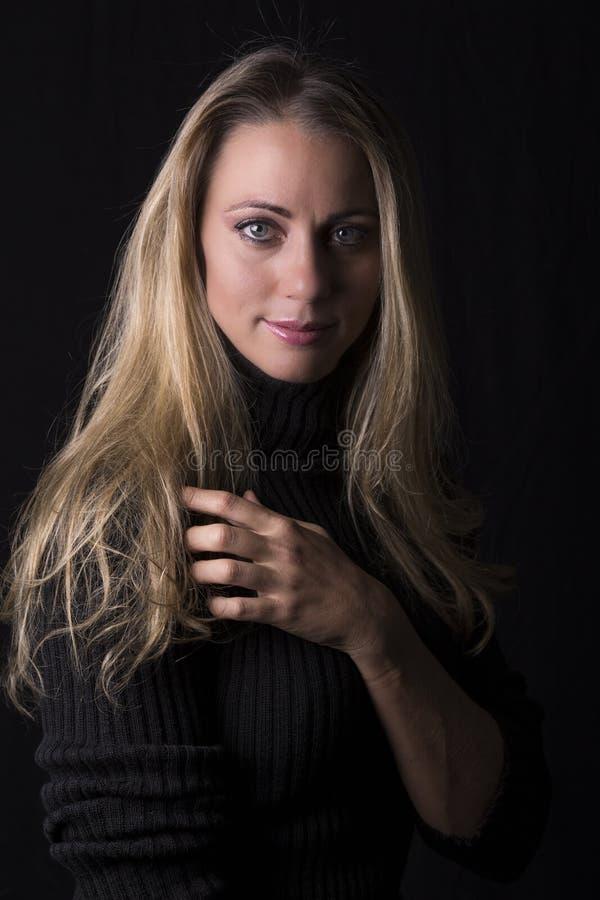 Retrato bonito da mulher na luminosidade reduzida que senta-se no sofá de couro marrom imagens de stock royalty free