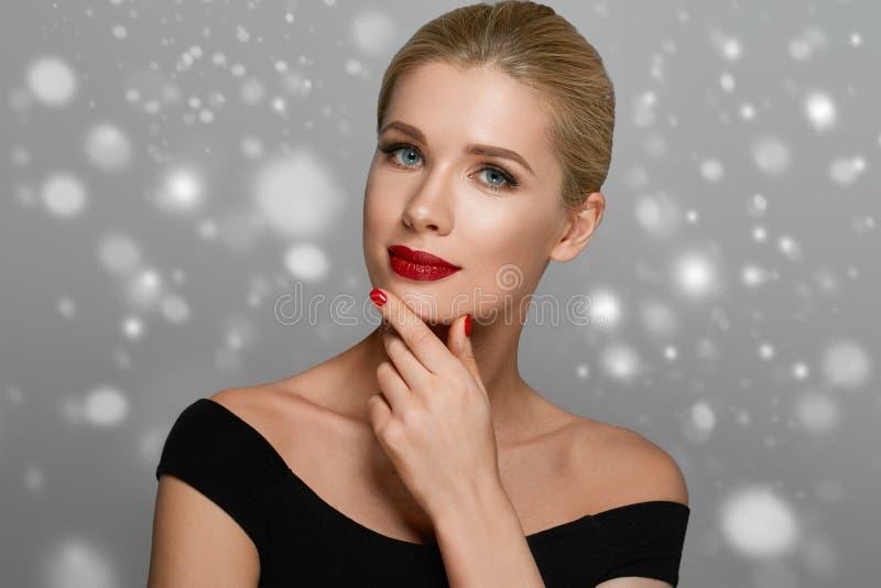 Retrato bonito da mulher no vestido sobre o fundo cinzento do inverno da neve foto de stock royalty free