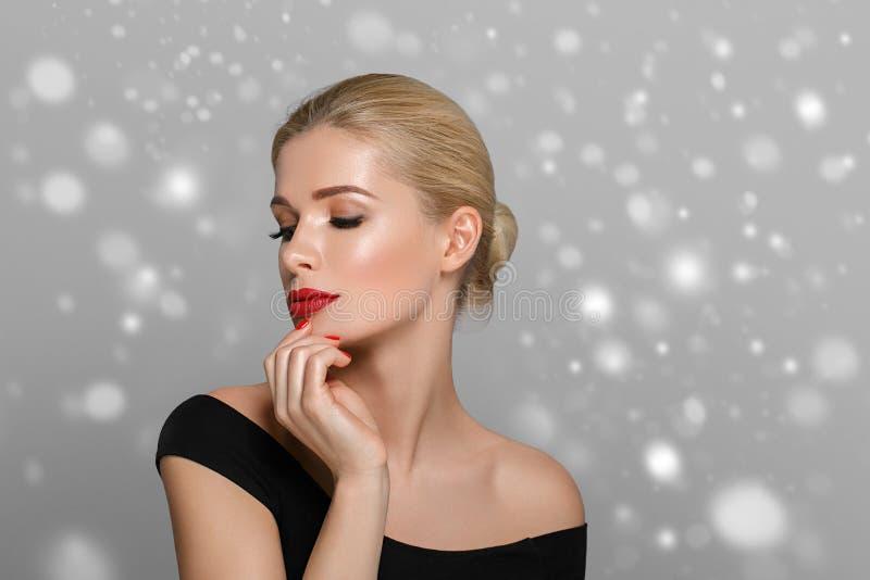 Retrato bonito da mulher no vestido sobre o fundo cinzento do inverno da neve imagem de stock