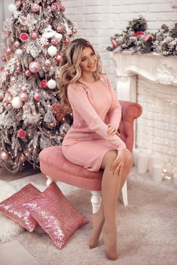 Retrato bonito de la muchacha de la Navidad Actual caja de regalo femenina hermosa Mujer rubia feliz en paño rosado con el pelo l foto de archivo libre de regalías