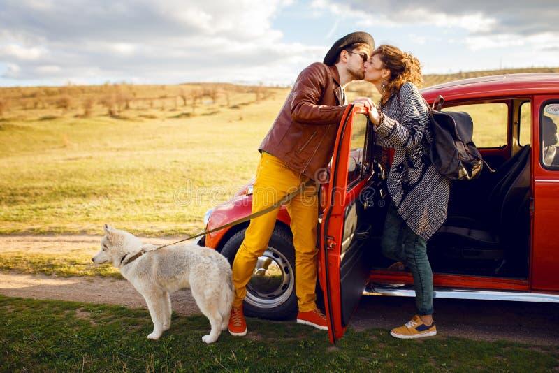 Retrato bonito de pares novos, perto do carro vermelho do vintage, com seu cão ronco, isolado em um fundo da natureza fotos de stock royalty free