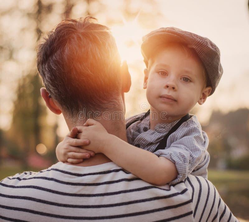 Retrato bonito de um rapaz pequeno bonito que abraça seu paizinho imagens de stock royalty free