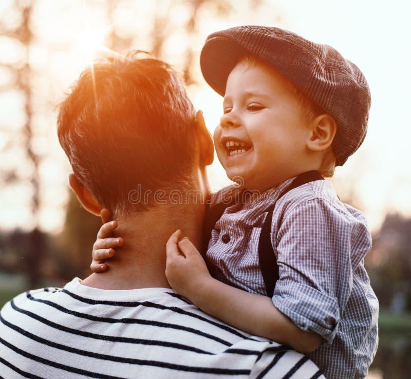 Retrato bonito de um rapaz pequeno bonito que abraça seu paizinho imagens de stock