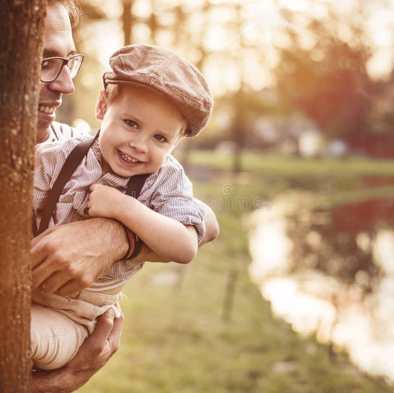 Retrato bonito de um rapaz pequeno bonito que abraça seu paizinho fotografia de stock royalty free