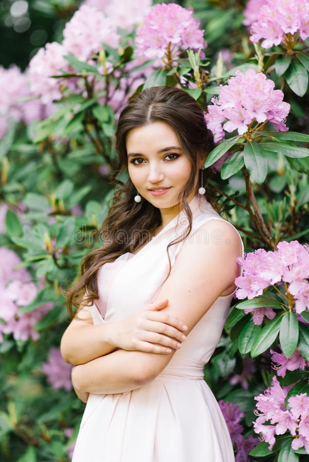 Retrato bonito de uma menina bonita que esteja cercada pelo rododendro de florescência das flores cor-de-rosa lilás na primavera  foto de stock