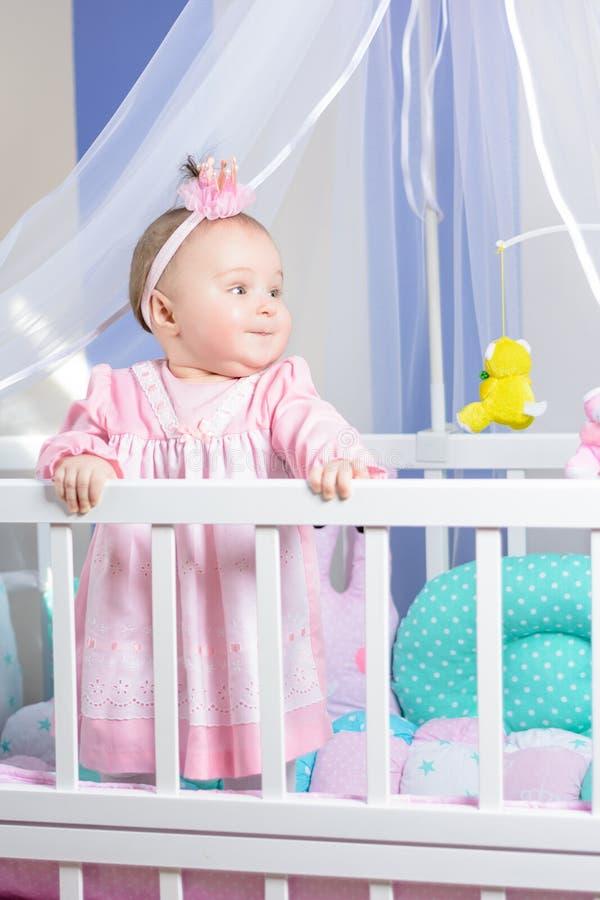 Retrato bonito de uma menina em um vestido cor-de-rosa em um berçário imagem de stock