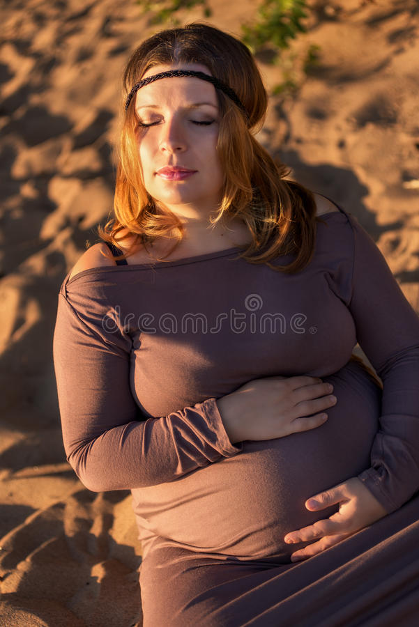 Retrato bonito de uma mulher gravida na areia imagens de stock