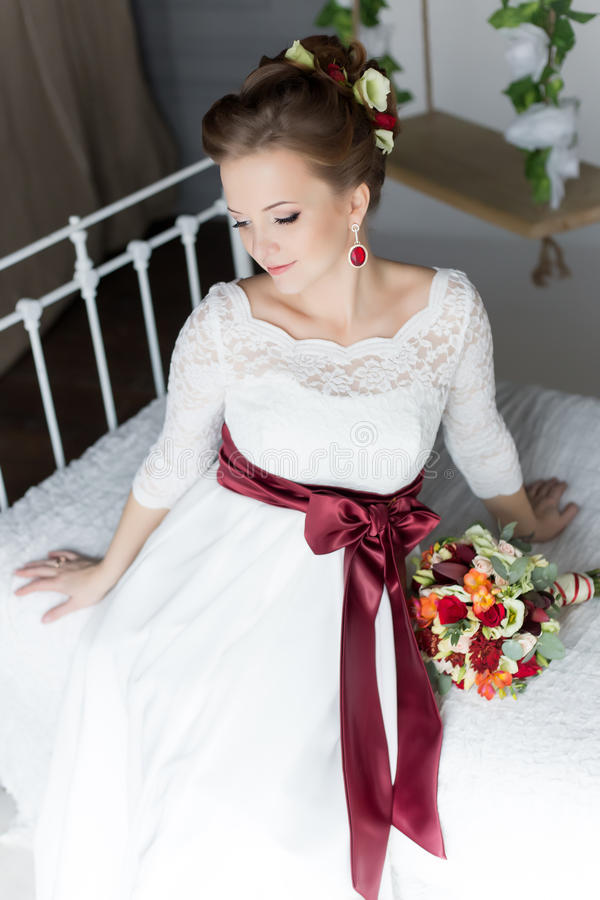 Retrato bonito de uma noiva feliz bonito delicada em um vestido branco com um ramalhete colorido pequeno brilhante imagem de stock