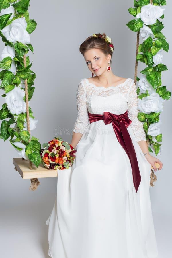 Retrato bonito de uma noiva feliz bonito delicada em um vestido branco com um ramalhete colorido pequeno brilhante fotografia de stock royalty free