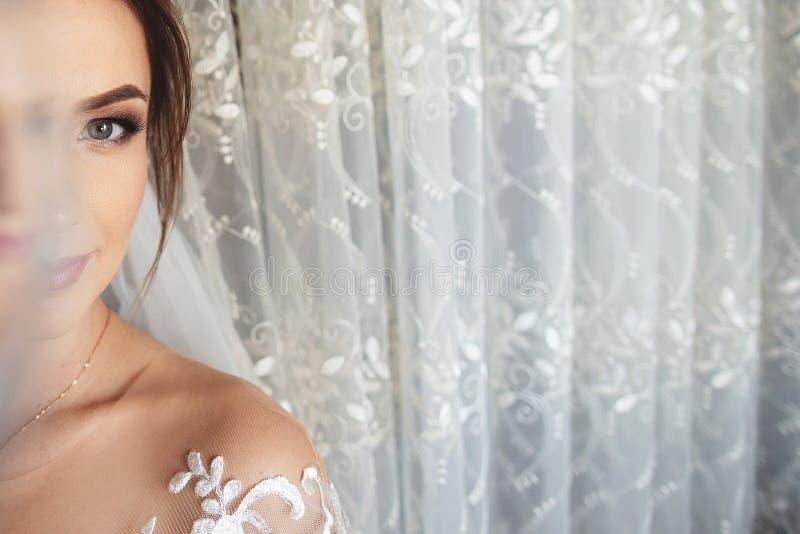 Retrato bonito do close up da noiva Suporte da menina no vestido de casamento luxuoso perto da janela foto de stock royalty free
